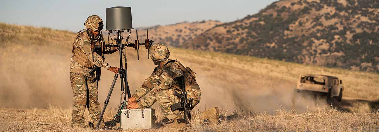 Two men setup TCI Model 903S, a compact, man-portable communications intelligence (COMINT) and direction finding (DF) system